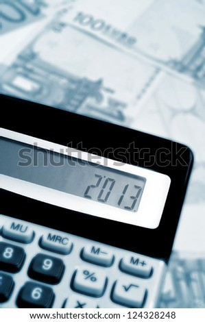 number 2013, as the new year, on the display of a calculator, with some euro bills in the background - stock photo