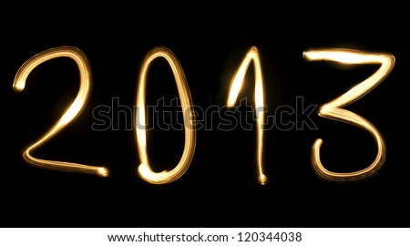 number 2013, as the new year, written with light beam on a black background - stock photo