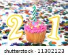 Number 21 celebration cupcake with candle and sprinkles.  Confetti in background. - stock photo