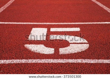 Number five. Big white track number on red rubber racetrack. Gentle textured running racetracks in small stadium.