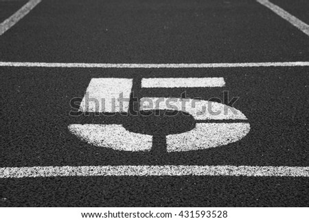 Number five. Big white track number on red rubber racetrack. Gentle textured running racetracks in small stadium. Black and white photo - stock photo
