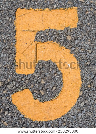 number five painted bright yellow paint on a gray rough pavement - stock photo