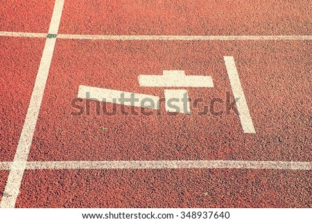 Number four. White track number on red rubber racetrack, texture of racetracks in small stadium - stock photo