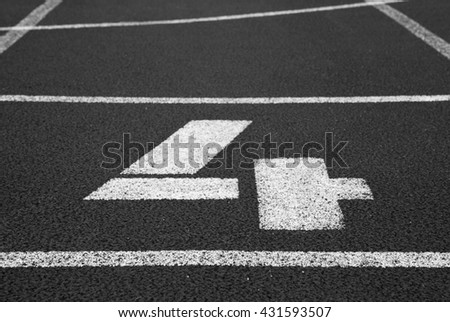 Number four. White track number on red rubber racetrack, texture of racetracks in small stadium. Black and white photo