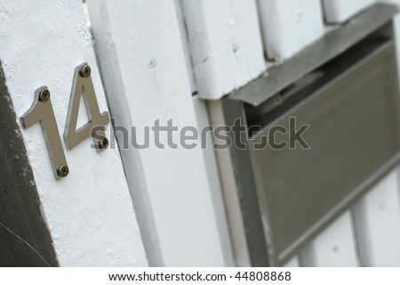 number fourteen sign for home with mailbox on white picket fence - stock photo