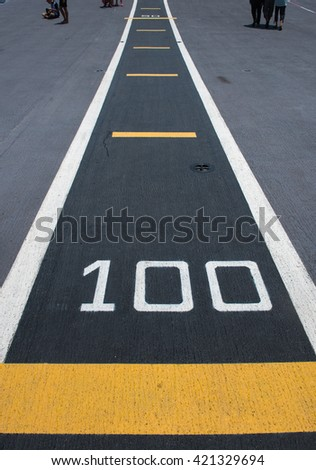 number hundred on white and yellow runway. - stock photo