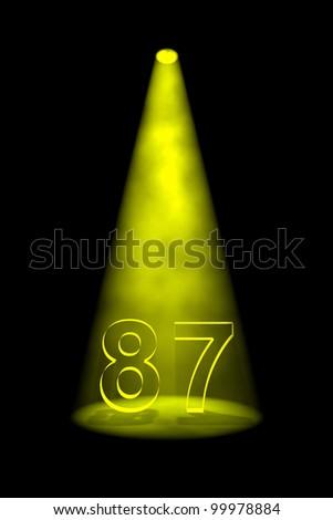 Number 87 illuminated with yellow spotlight on black background - stock photo