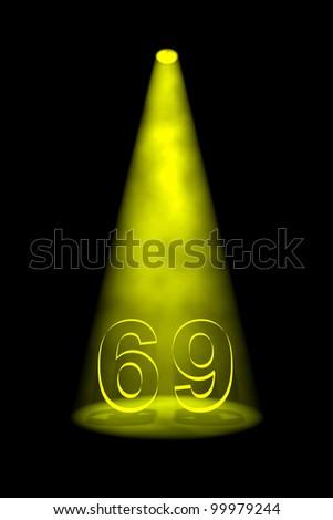Number 69 illuminated with yellow spotlight on black background - stock photo