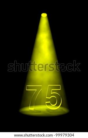 Number 75 illuminated with yellow spotlight on black background - stock photo