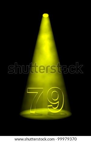 Number 79 illuminated with yellow spotlight on black background - stock photo