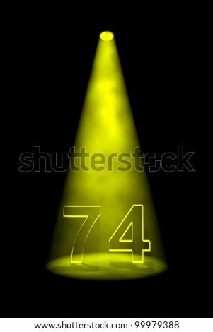 Number 74 illuminated with yellow spotlight on black background - stock photo