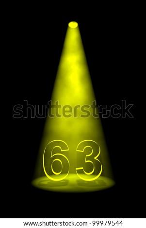 Number 63 illuminated with yellow spotlight on black background - stock photo