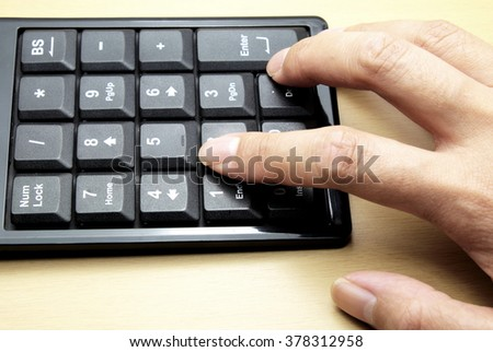 Number keyboard of computer on wooden floor/table, female hand and pressing fingers on buttons. Space for texts. - stock photo