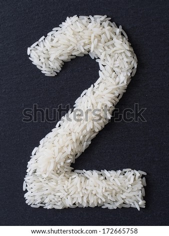Number 2 made of rice on a black slate - stock photo