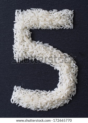 Number 5 made of rice on a black slate - stock photo