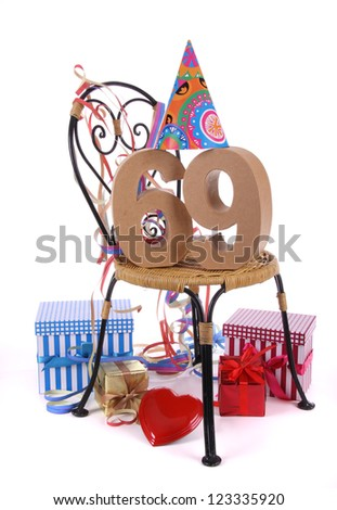 Number of age in a colorful studio setting with paper party hat and figures, a red heart and gifts
