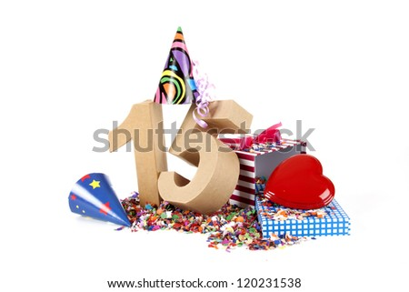 Number of age in a colorful studio setting with paper party hats, a red heart and gifts on a bottom of confettie