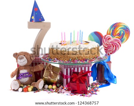 Number of age in a colorful studio setting with paper party hats, a red heart and gifts on a bottom of confetti and sweet cake with candles