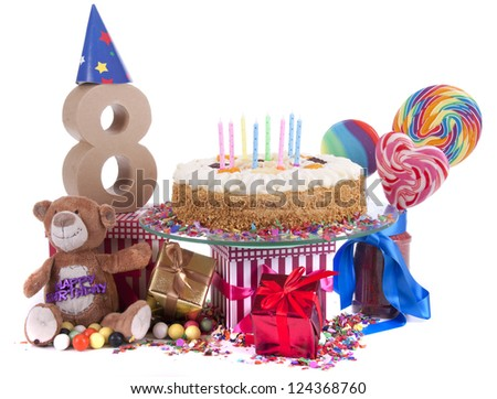 Number of age in a colorful studio setting with paper party hats, a red heart and gifts on a bottom of confetti and sweet cake with candles - stock photo