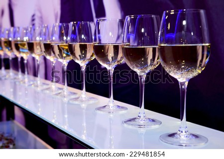 Number of glasses with white wine lit by nightclub lights on dark-purple background