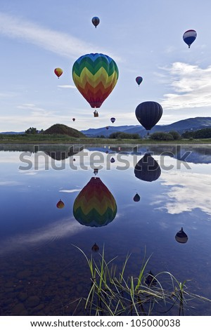 Number of Hot Air Balloons Launching Over a Lake. - stock photo