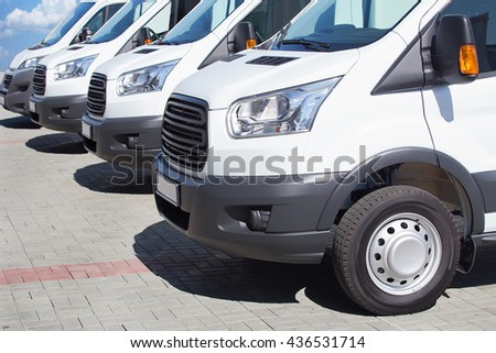 number of new white minibuses and vans outside - stock photo