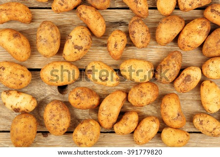number of raw baby potatoes on wood - stock photo