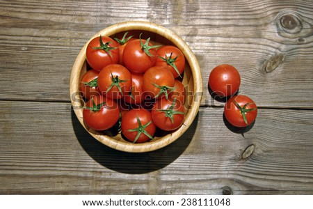 number of tomatoes cherrys on a wooden bowl - stock photo
