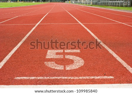 number 5 on red running track - stock photo