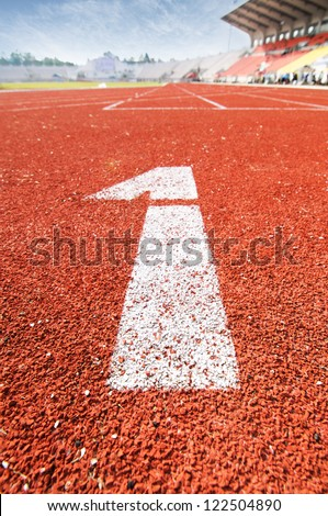 """number """"1"""" on red running track. - stock photo"""