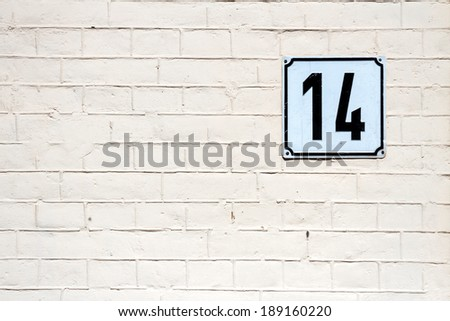Number 14 on textured brick wall