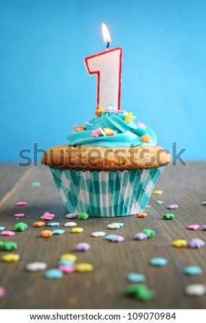 Number one birthday candle on a blue cupcake on blue background - stock photo