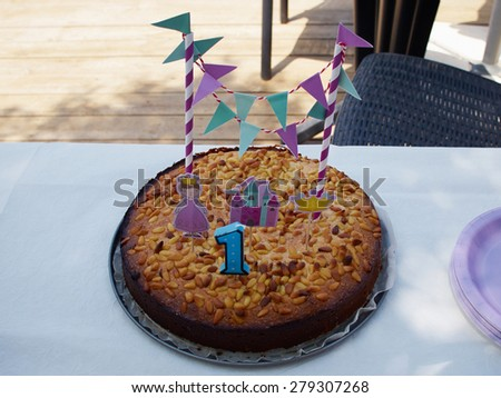 Number one birthday candle on a cake in a family garden party - stock photo