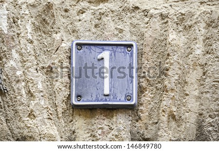 Number one, details of a number one on a wall in the city, signal and information - stock photo