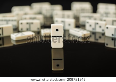 Number One domino in front of peers as concept image for success, innovation, leadership, winning and leader of the pack - stock photo