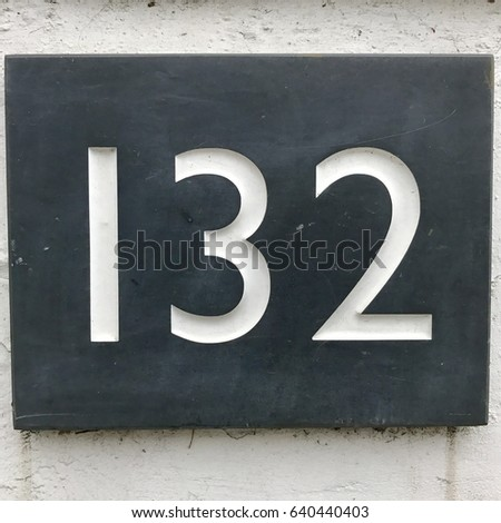 Number 132 one hundred and thirty two carved stone house number address sign on painted white stone wall textured background
