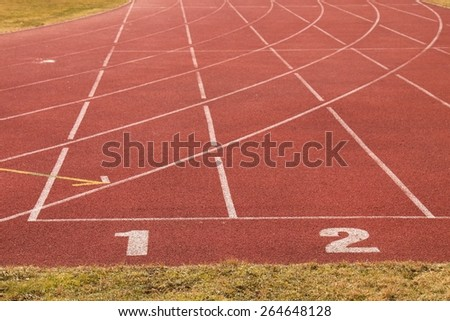 Number one. Number two. White track number on red rubber racetrack, texture of running racetracks in small stadium - stock photo