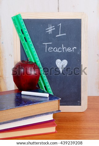 Number one teacher is written on a messy black chalkboard with old books in front. A red apple sits on top of the books with a piece of white chalk. Scene also includes a green ruler.