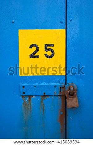 Number 25 printed on weathered industrial steel doorway to lockup.  - stock photo