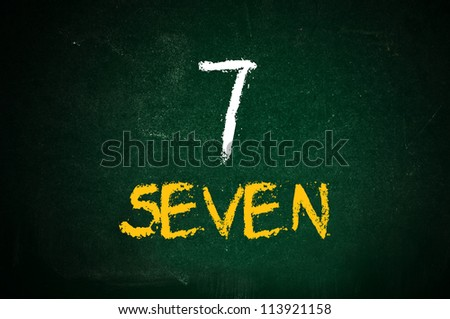 Number seven, handwritten number seven with a chalk on a green chalkboard.