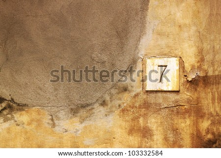 Number seven (7) on an ancient wall of stone - stock photo