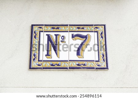 Number seven on the wall of a house, detail of a number of information, odd number - stock photo
