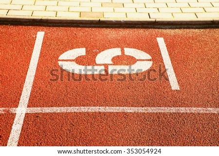 Number six. White athletic track number on red rubber racetrack, texture of racetracks in small stadium - stock photo