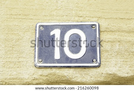 Number ten on the wall of a house, detail of a number of information, even number - stock photo
