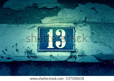 Number thirteen on a wall, detail of a number of information in a house