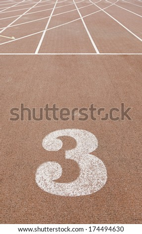 Number three on a running track, a track detail for running outdoors, sport and healthy living, competition - stock photo