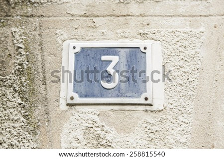 Number three on the wall of a house, number of information, odd number - stock photo