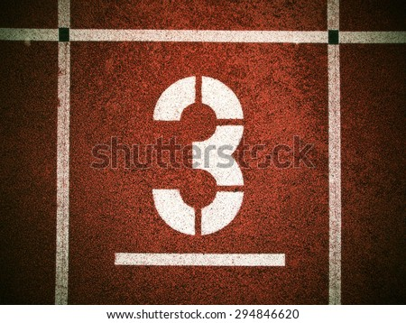 Number three. White track number on red rubber racetrack, texture of running racetracks in small stadium - stock photo
