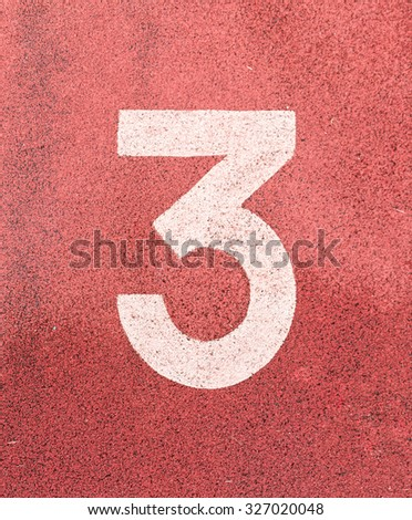 Number three,White track number on rubber racetrack, texture of running racetracks in small stadium. - stock photo