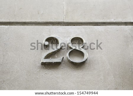 Number twenty-eight on the wall, detail of a number of information on a street, numbers - stock photo